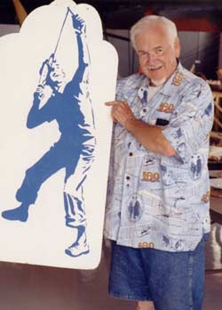 Frank Macy holding his artistic representation of a boy launching the folding wing Interceptor