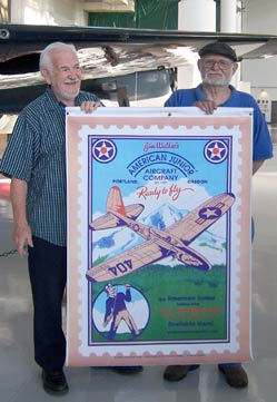 Frank Macy and Gil Coughlin hold an American Junior poster designed by Frank Macy